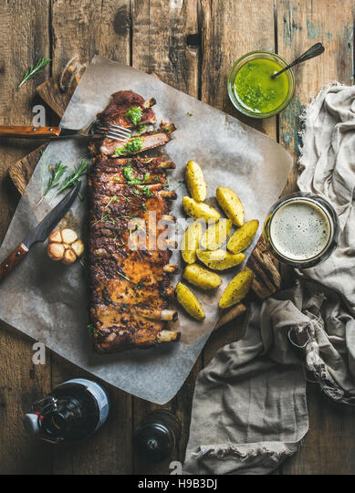 Roasted pork ribs with spices, fried potato and dark beer - Stock Image
