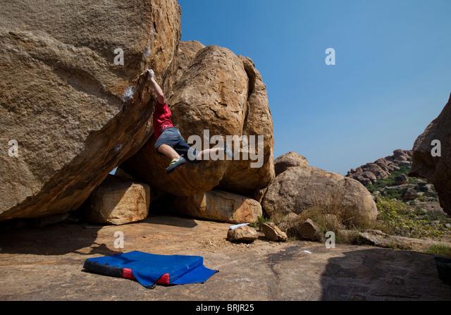 Caucasian male climber cutting loose on a highball boulder in Hampi, India. - Stock-Bilder