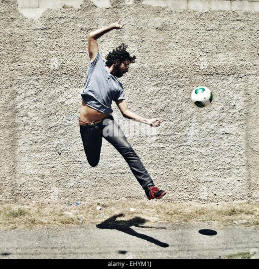 Mid adult man playing with football, Venezuela - Stock-Bilder
