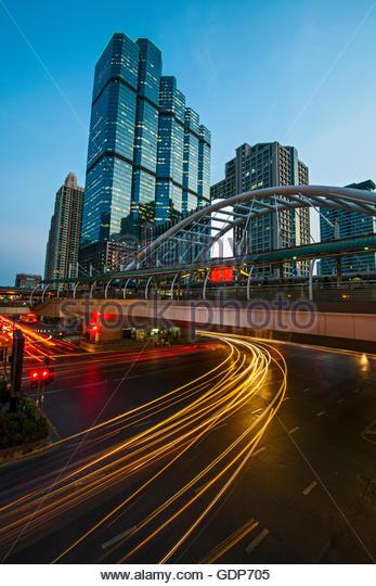 Light trails on road below footbridge, Sathorn, Bangkok, Thailand - Stock Image