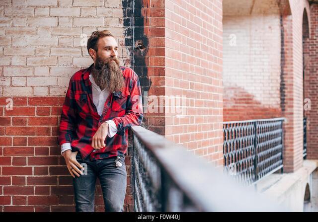 Man with beard leaning on balcony looking away - Stock-Bilder