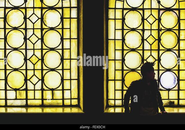 Man Standing By Yellow Glass Window - Stock Image