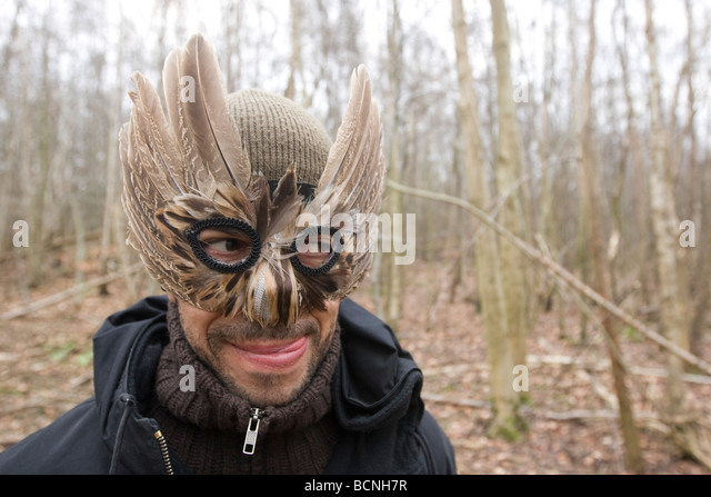 Man in feather mask licks his lips - Stock Image