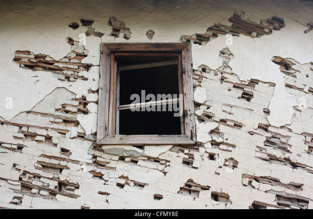 A window without glass located on the cracked and crumbling wall. - Stock Image