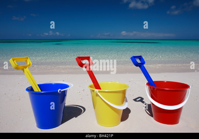Three toy buckets and spades in a line on a tropical beach - Stock Image