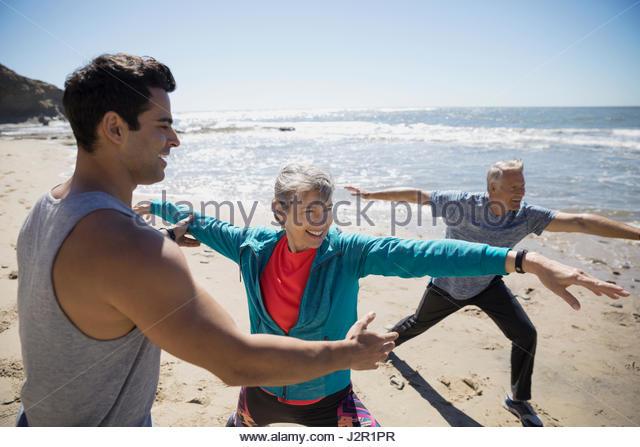 Crossfit trainer helping senior couple exercising, practicing yoga warrior 2 pose on sunny beach - Stock Image