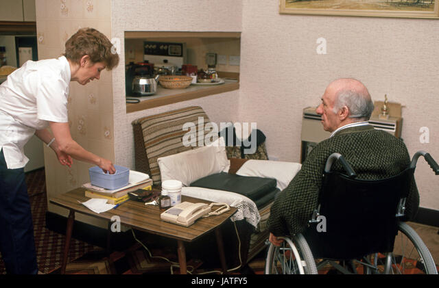 home help carers district nurse on a home visit to elderly man in sheltered accommodation - Stock Image