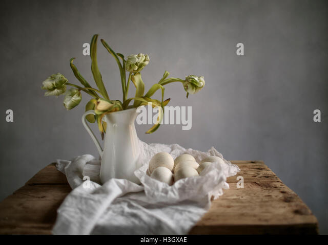 Still Life with Tulips and Eggs on wooden Table - Stock Image