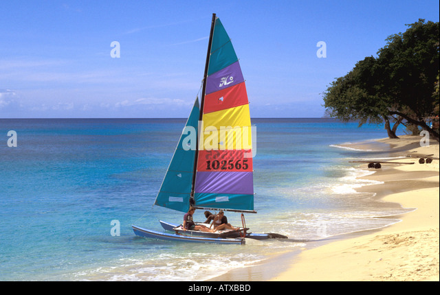 Barbados beach people in Small Catamaran Leaving Beach Caribbean - Stock Image