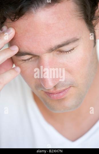 Head shot of man scowling - Stock Image