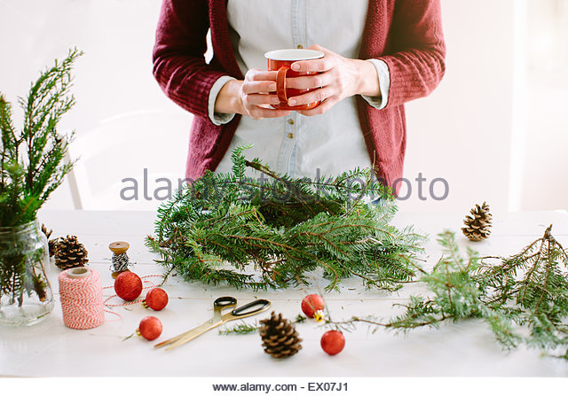 Woman decorating Christmas wreath - Stock Image