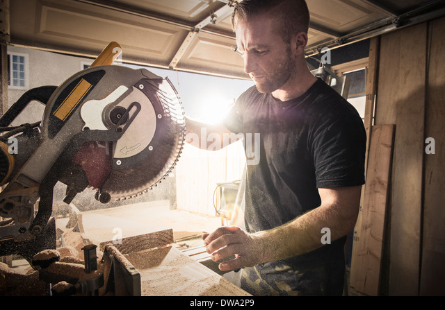 Male carpenter working with a rotary saw in workshop - Stock Image