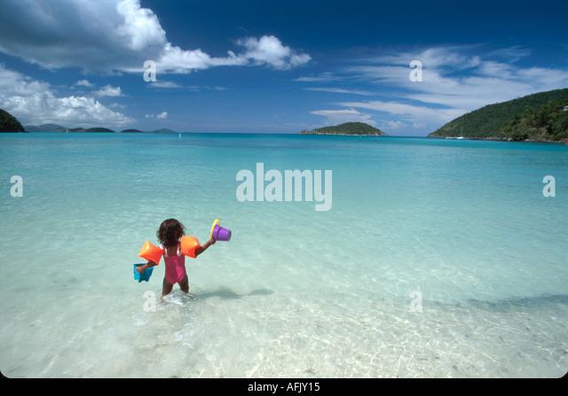 US Virgin Islands St. John Virgin Islands National Park Maho Beach Maho Bay child plays in surf USVI011 - Stock Image