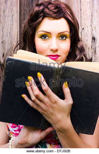 Beautiful Female College Or University Student Reading Old Open Textbook Or Book While Studying Outdoor In An Exam - Stock Image