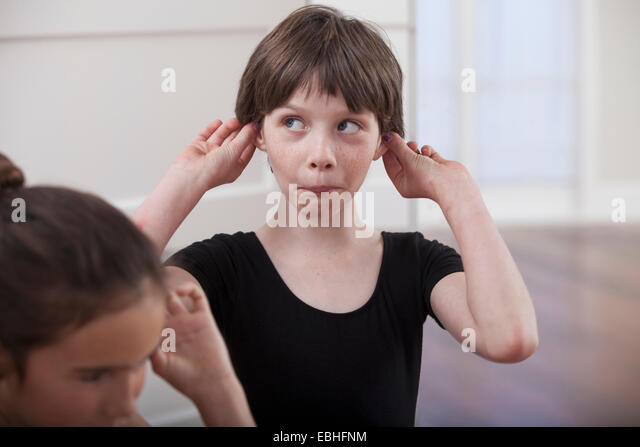Girl with holding ears pulling a face in ballet school - Stock Image