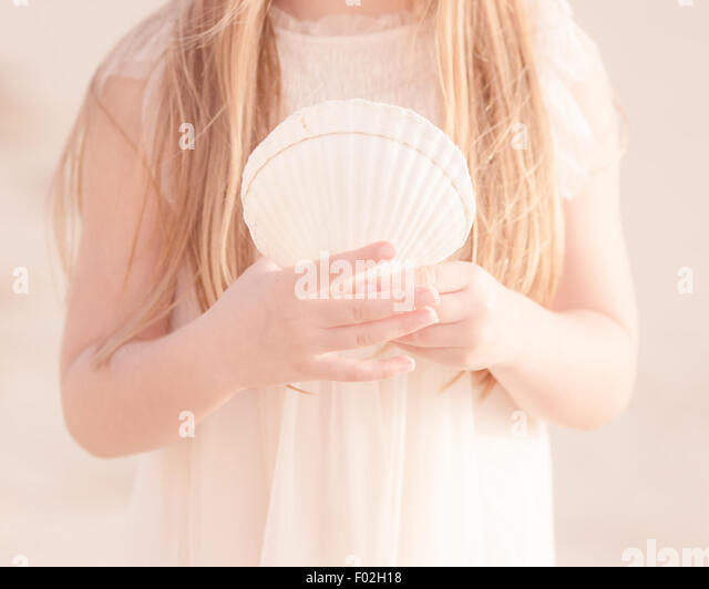 Close-up of a girl holding  seashell - Stock Image