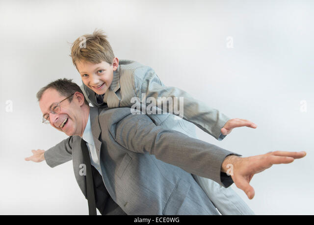 Father giving piggy back ride to his son, smiling - Stock Image