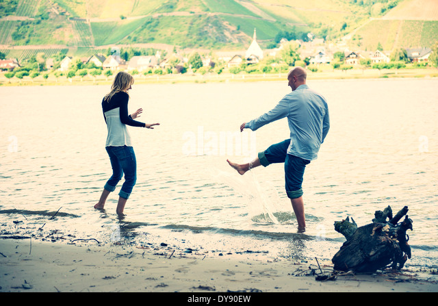 Young couple having fun at waterside of Rhine river - Stock Image