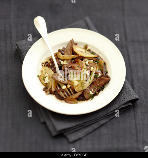 Beef,onion and fennel wok with flaked goat's cheese - Stock Image