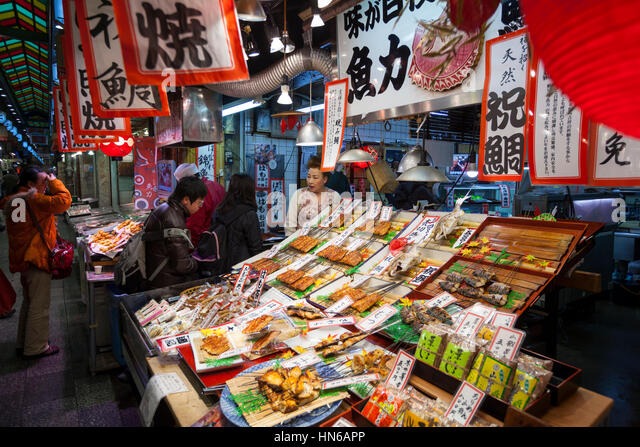 KYOTO, JAPAN - MARCH 23: Staff and customers at a stall selling cooked fish in Nishiki food market in Central Kyoto - Stock Image