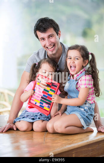 Portrait of happy father and daughters playing with abacus in house - Stock Image