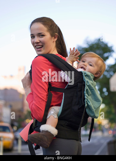 Young woman carrying her baby in a baby carrier, New York City, New York State, USA - Stock Image