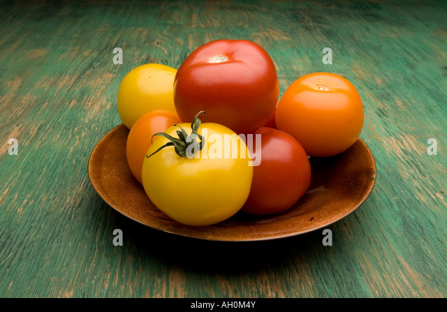 Ripe tomatoes in bowl on table - Stock Image