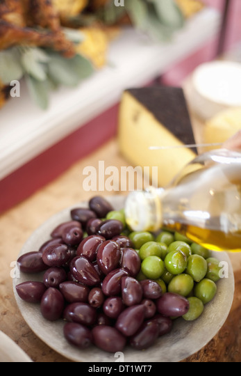 fresh organic vegetables Green and black olives drizzling of olive oil from a bottle Prepared farm stand foods for - Stock Image
