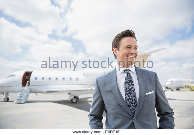 Businessman on tarmac with corporate jet - Stock Image
