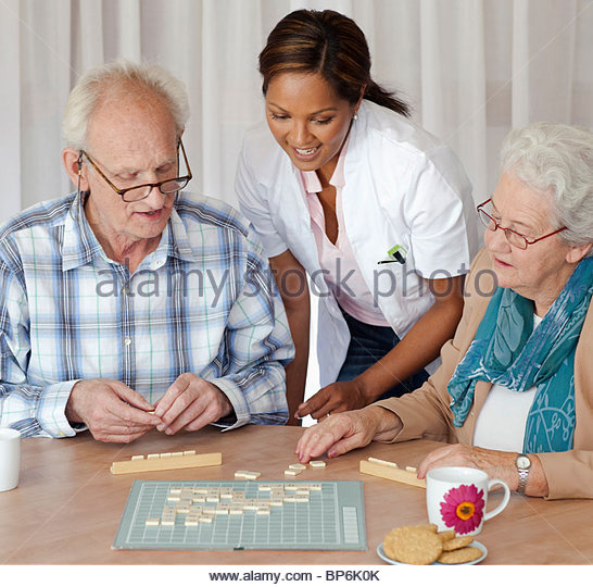A senior couple and care assistant playing a board game together - Stock Image