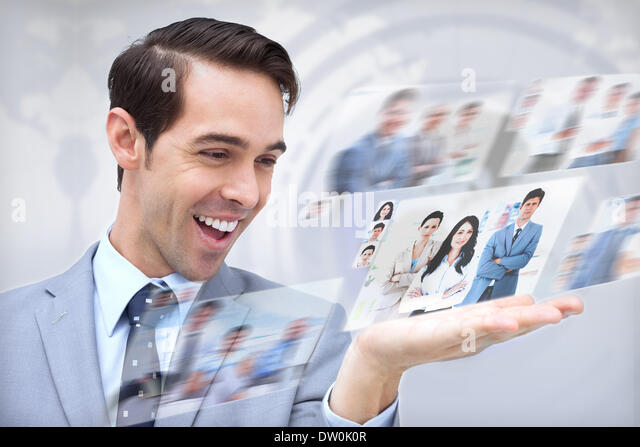 Joyful businessman looking at pictures - Stock Image