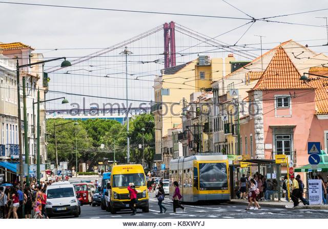 Portugal Lisbon Belem historic district Rua de Belem buildings street crossing traffic tram view of Ponte 25 de - Stock Image
