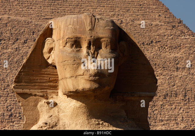 'Close up' of front facing Great Sphinx head, Pyramid of Khafre in background, Giza, Cairo, Egypt - Stock Image