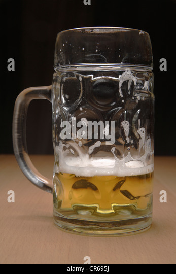 Half full beer mug on table, close up - Stock Image