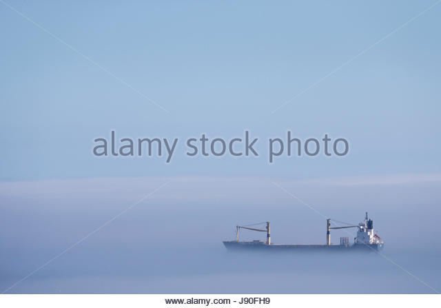 Container Ship At Sea In Morning Mist - Stock-Bilder