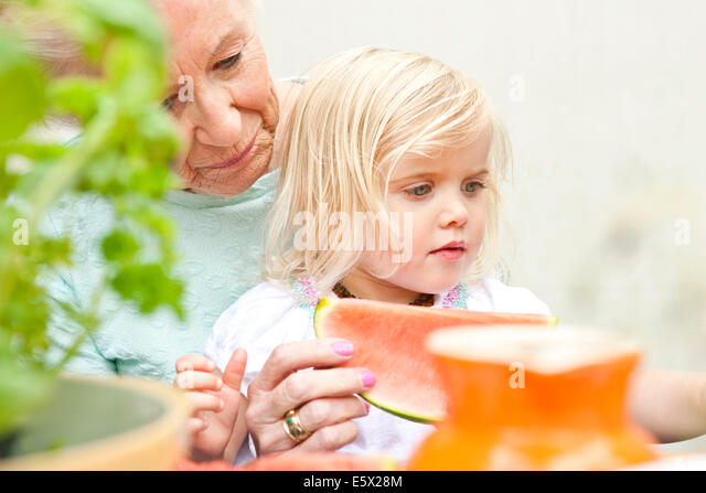 Senior woman and toddler great granddaughter eating melon slice at garden table - Stock Image