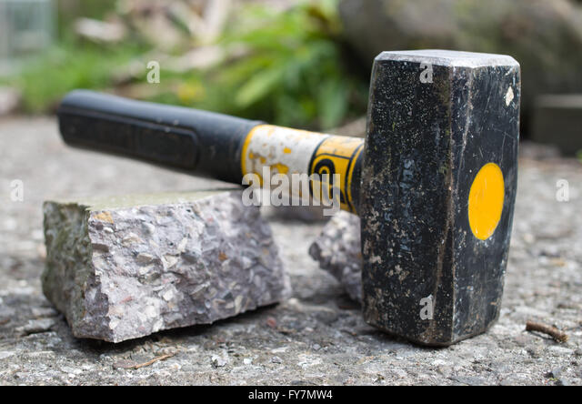 Breaking up concrete with lump hammer. - Stock Image