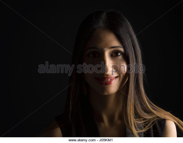 Portrait smiling Indian woman with bindi against black background - Stock Image
