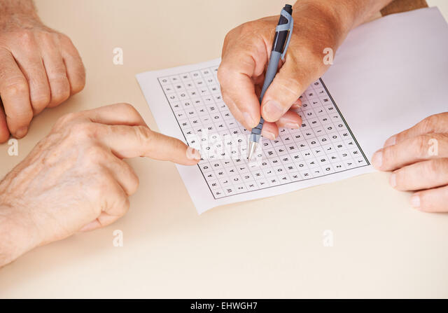 Hands of two senior people solving together a word search quiz - Stock-Bilder