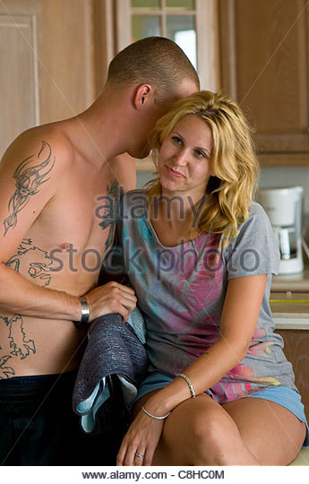 A young couple morning after their wedding whisper in the kitchen. - Stock-Bilder