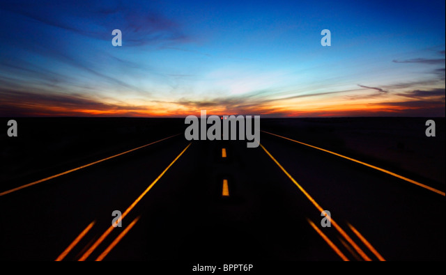 Night highway with dramatic sky & car lights in motion - Stock Image