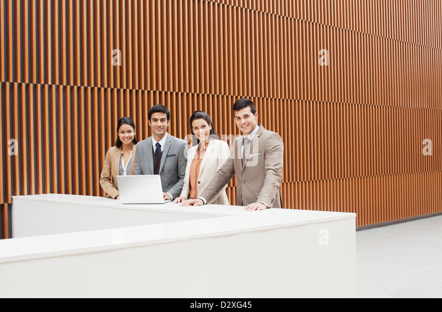 Portrait of confident business people with laptop at ledge in office - Stock Image