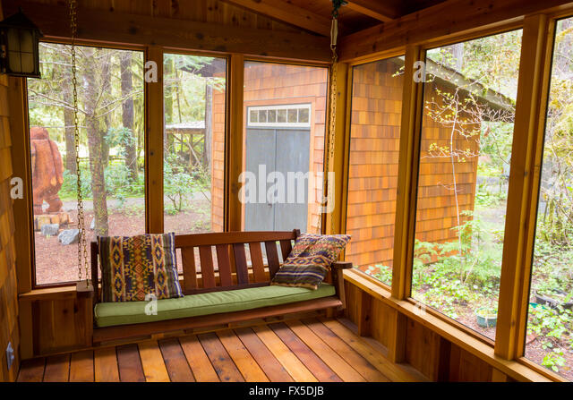 Bench swing hung by chain looking comfortable on a screened in porch. - Stock Image