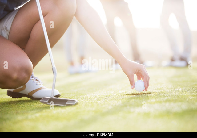 Woman removing golf ball from hole - Stock Image