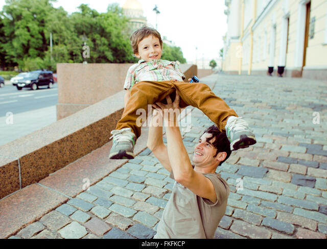little son with father outside hagging and smiling, city lifestyle concept - Stock-Bilder