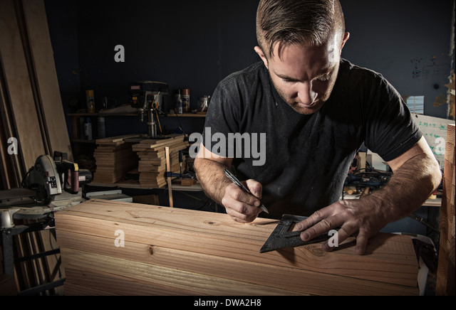 Male carpenter measuring wooden plank with set square in workshop - Stock Image