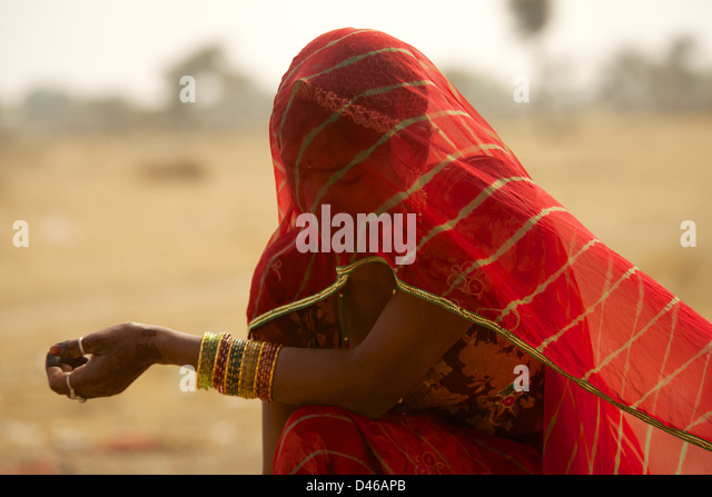 A young Indian woman on the outskirts of Bikaner in Rajasthan northern India. shields her face from the desert winds - Stock-Bilder