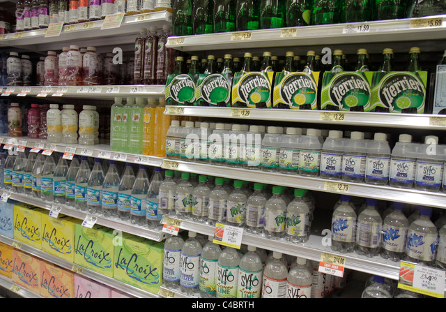 Ocala Florida Publix grocery store supermarket retail display packaging competing brands bottled water shelf shelves - Stock Image