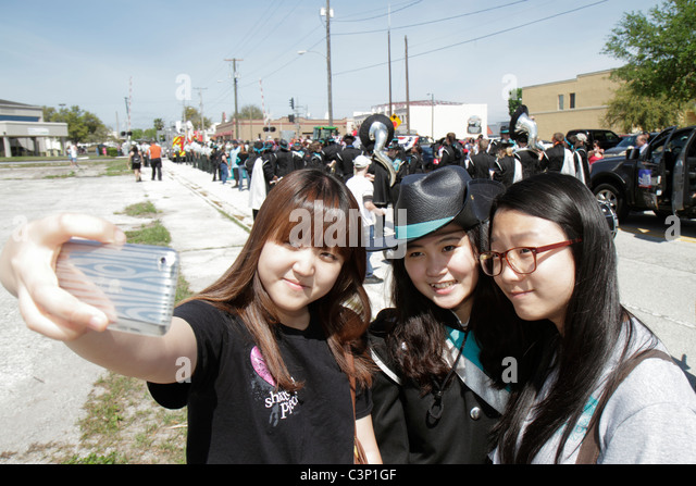 Plant City Florida South Evers Street Florida Strawberry Festival Grand Parade Asian girl teen student pocket camera - Stock Image