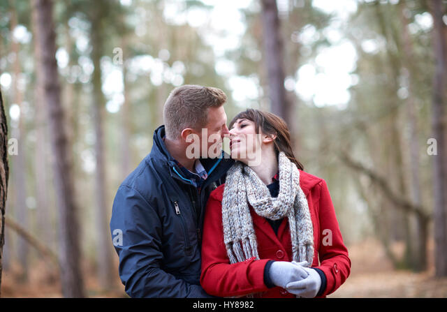 A young couple embrace during a walk in the woods - Stock Image